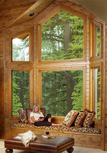 Woman relaxing reading a book in a wood cabin, reading nook