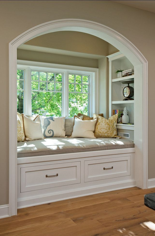 Great reading bay window reading nook with throw pillows and cushion, painted in white.