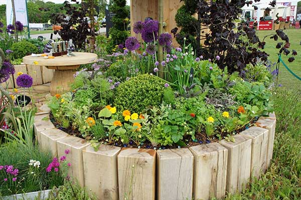 DIY Round Wood Flower and Herb Bed #flowerbed #flowerpot #gardens #gardenideas #planter #gardeningtips #decorhomeideas
