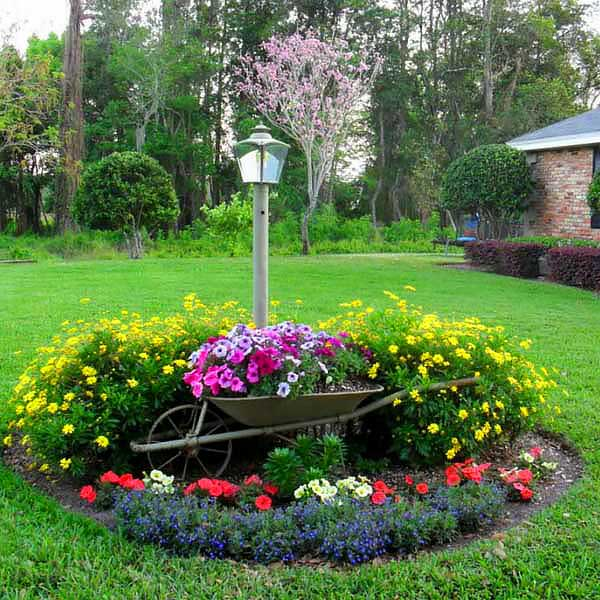 Round small flowers garden idea with recycled wheel barrow. #gardens #gardening #gardenideas #gardeningtips #landscapedesign #decorhomeideas