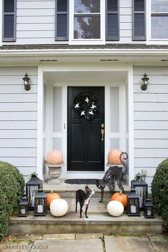 Front porch Halloween decorations with pumpkins in urns and cats #halloweendecorations #halloween #diyhalloween #halloweendecor #decorhomeideas