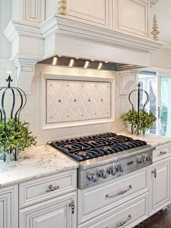 antique white kitchen cabinets with detailed embellishments are highlighted by granite countertops, a matching white range hood and a bright white tile backsplash