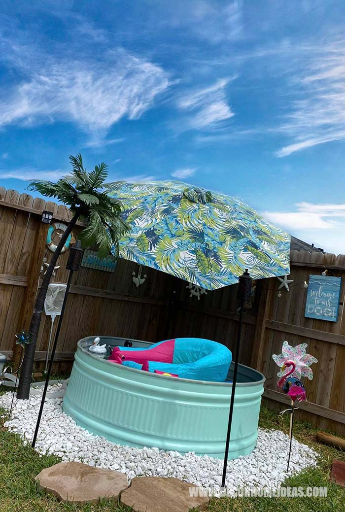 DIY Stock Tank Pool With Fake Palm And Umbrella