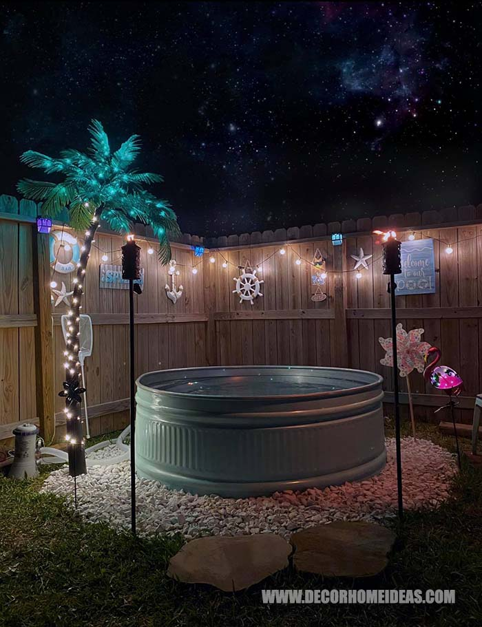How To DIY Stock Tank Pool Idea. How it looks at night with fake palm tree and string lights around it. #stocktankpool #pool #decorhomeideas