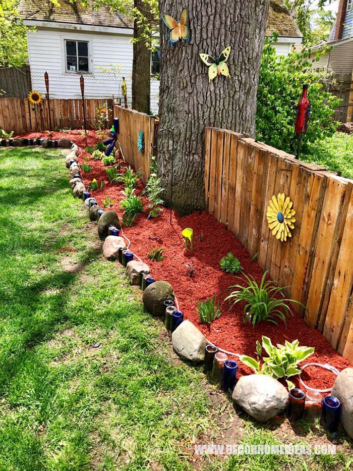 Small Garden Bed Edging Made of Rocks And Bottles. Nicely running along a wooden fence decorated with sunflowers and butterflies. #smallgarden #edging #decorhomeideas