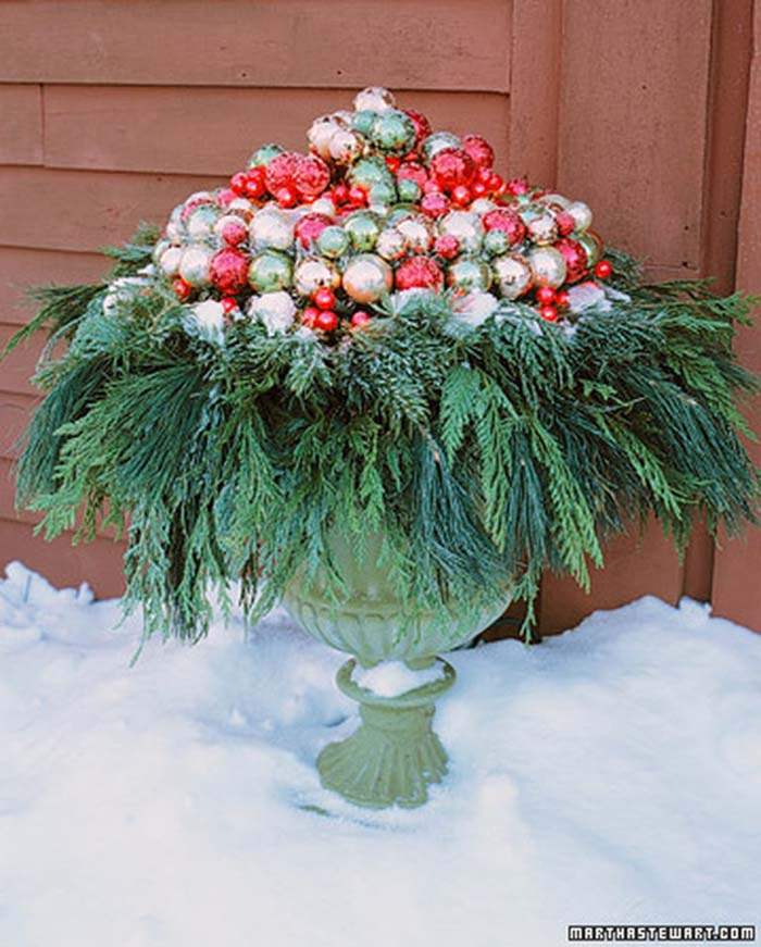Red, Green, and Gold Baubles in a Bed of Greens #Christmas #urns #decorations #decorhomeideas