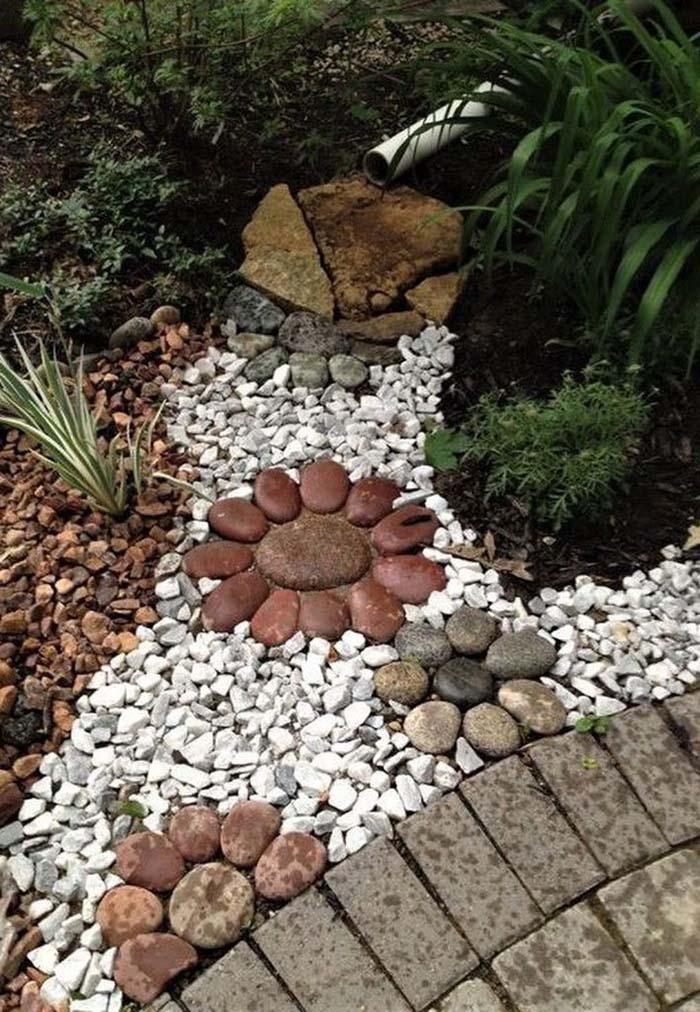 Large Flowers on Colorful Rock Bed #riverrocklandscaping #decorhomeideas